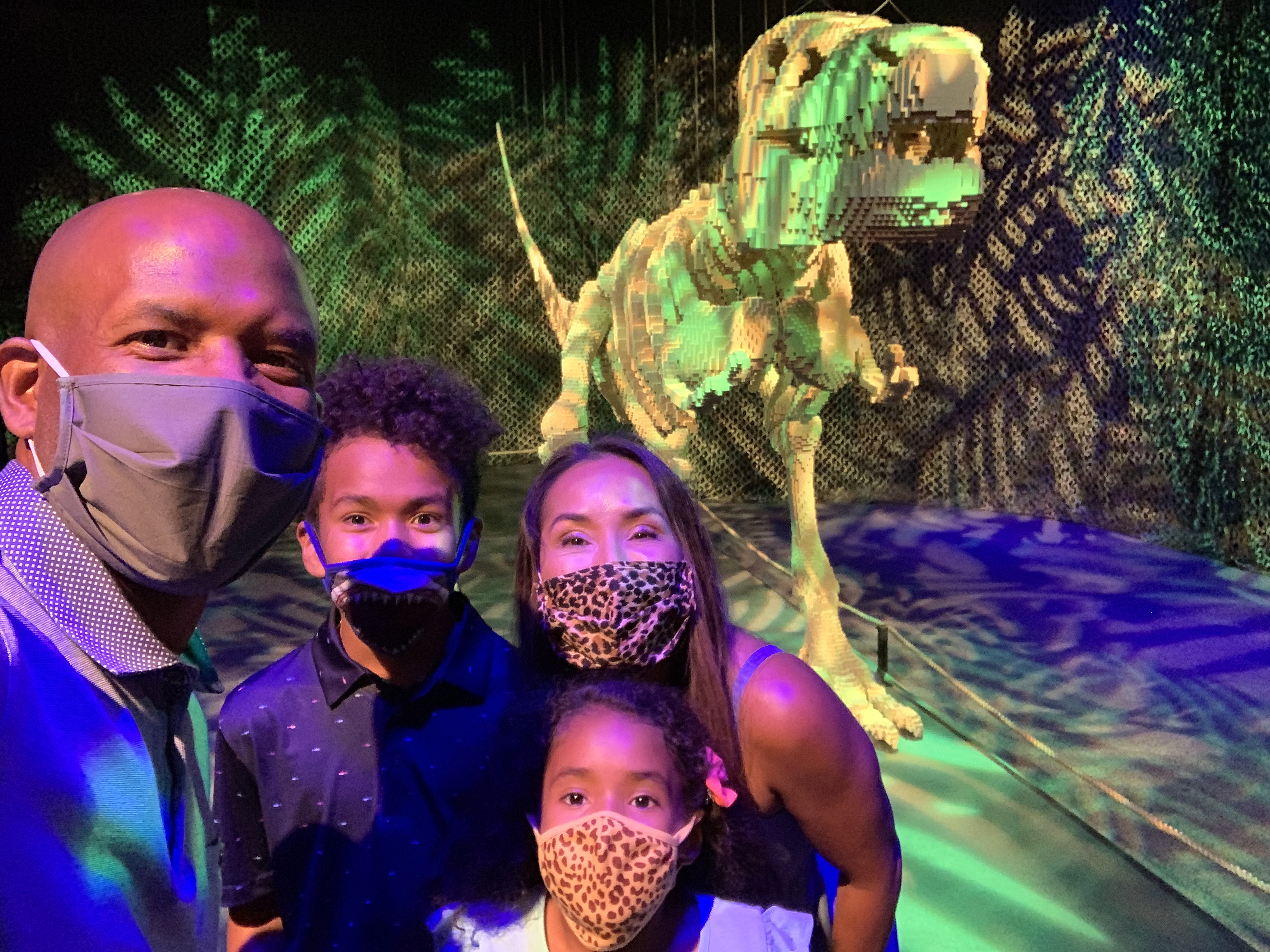 Diverse family with face masks taking a selfie in front of T-Rex sculpture in The Art of the Brick exhibition